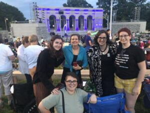 2 faculty members and three graduate students smiling in front of amphitheater for Shakespeare in the Park