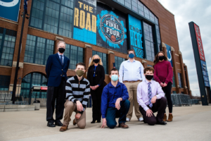 Picture of five journalism students and two professors in front of Lucas Oil Stadium