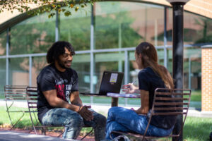 Two students sit in courtyard studying together