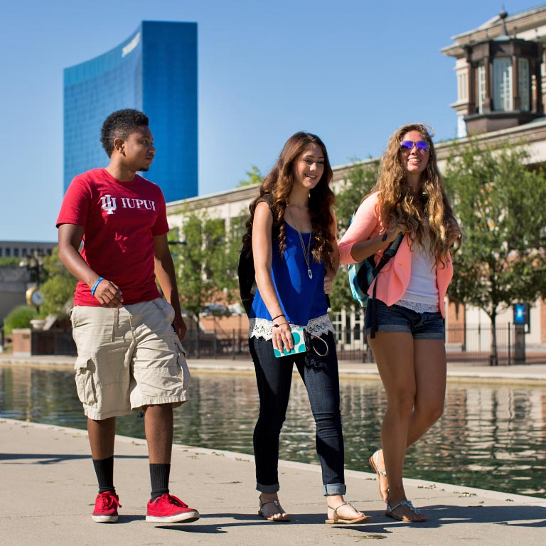 Three students walk by a canal. A tall building is in the background.