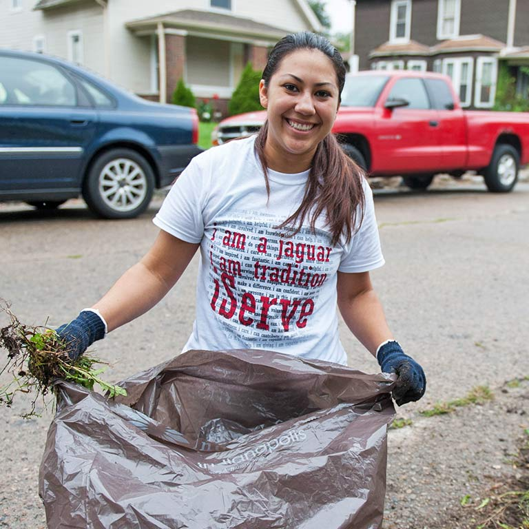 A student holds a large bag and a handful of yard waste. The text on her shirt says, 'I am a Jaguar, I am tradition, iServe.'