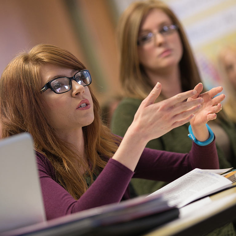 A student talks from her desk while other students listen.