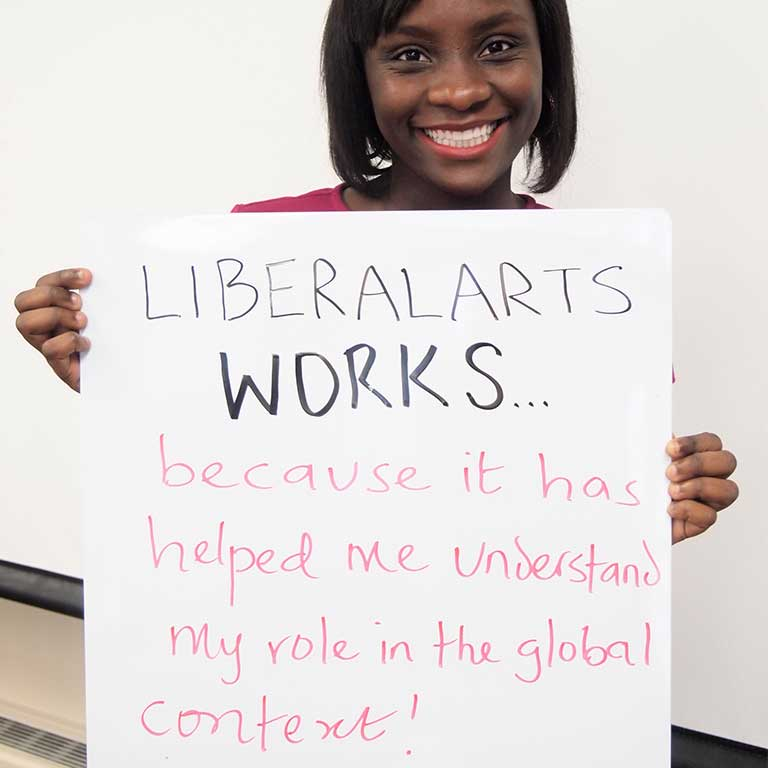 A female student holds up a handwritten sign that reads 'Liberal Arts Works...because it has helped me understand my role in the global context!'
