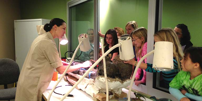 A female student in a lab coat shows a group of young girls a large dinosaur fossil.