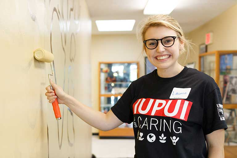 A female student paints a wall. She's wearing a shirt that says 'IUPUI Day of Caring.'