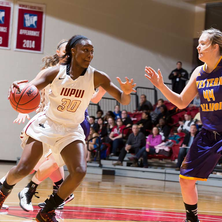 An IUPUI women's basketball player dribbles the ball during a game.