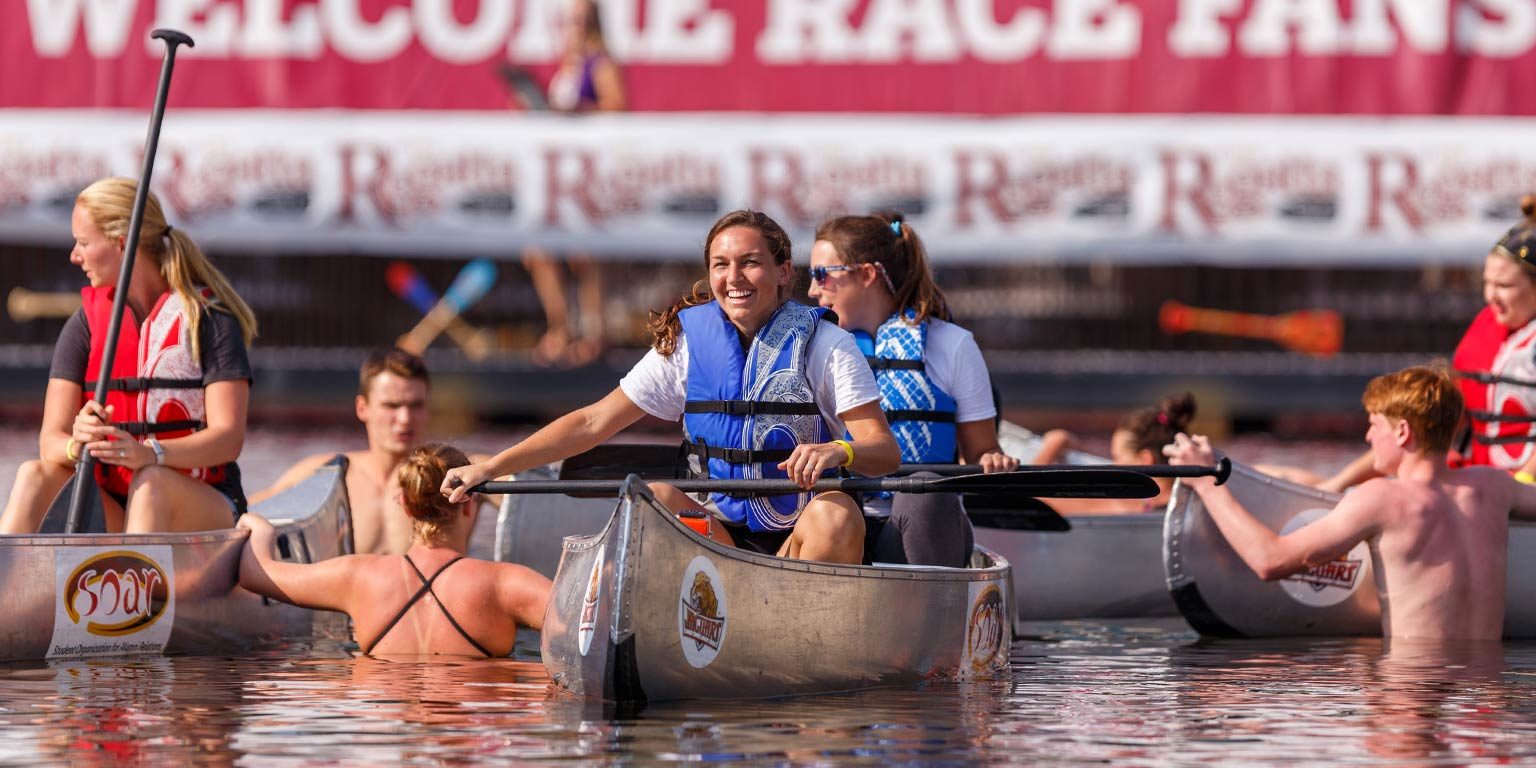 Students at the IUPUI Regatta sit in canoes on the water.