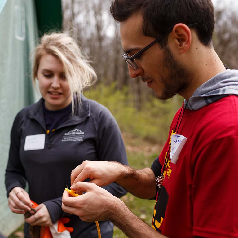 Students tie knots and work with camping equipment.