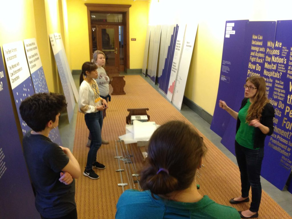 Dr. Laura Holzman and students install an exhibit at the Central Library in downtown Indianapolis.