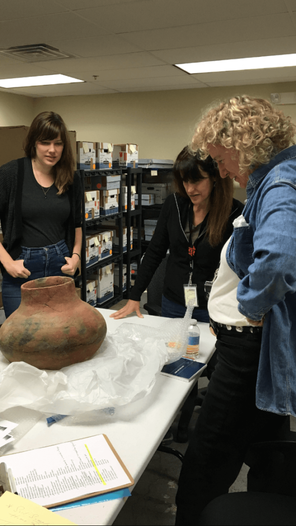 Dr. Holly Cusack-McVeigh and a student care for objects with the FBI Art Crime Team.