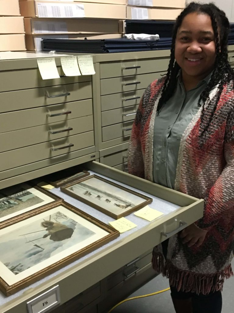 A student works in collection storage during her internship.
