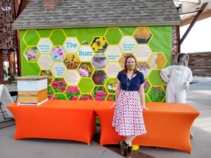 A person stands in front of an orange table with a bee hive and a model of a bee keeper in the background.