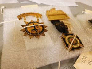 Masonic pins and badges tied to a foam base for archival storage
