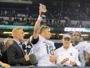 Michigan State quarterback Connor Cook holds the Grange-Griffin Championship Game MVP award before handing it to his offensive linemen.