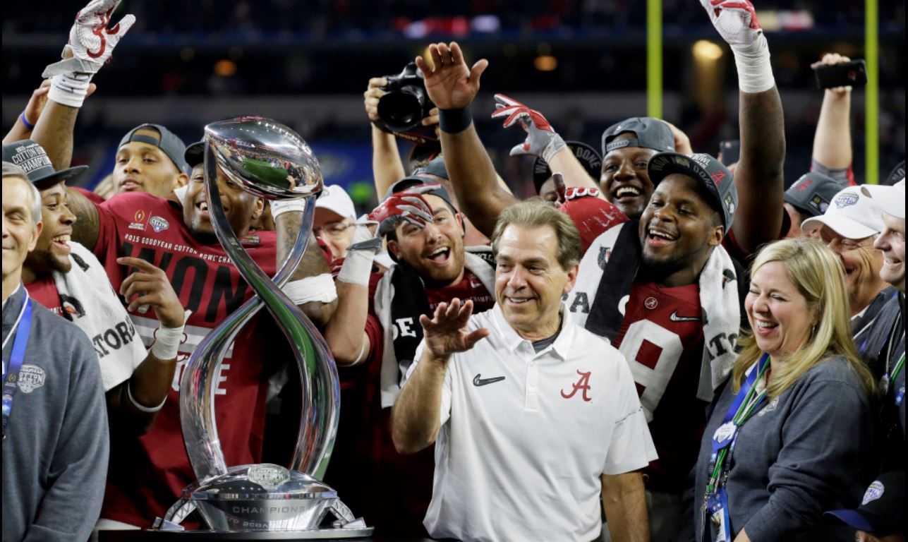 Alabama head coach Nick Saban and players are presented with the Cotton Bowl trophy following their 38-0 win over Michigan State. (AP photo)